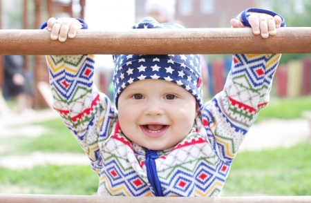 10 month: happy baby holding of climber on playground