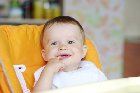 baby on chair: lovely baby sitting on baby chair on kitchen