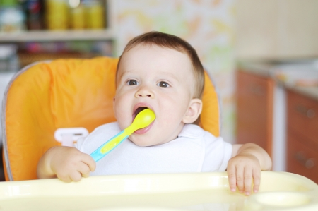 nice baby with spoon on kitchen photo