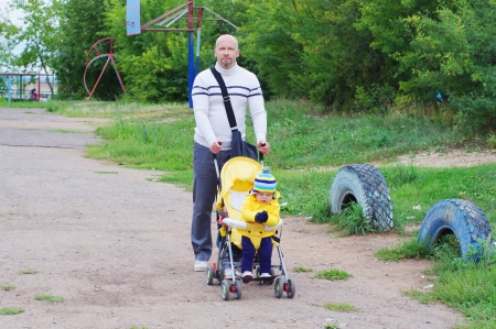 father and baby son age of 11 months walking photo