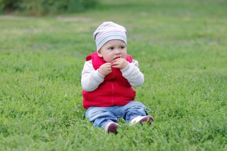 baby tastes wild apple sitting on grass  photo