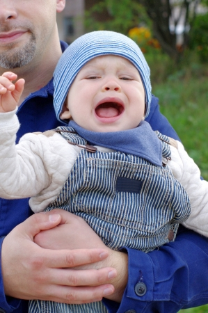 grieved: crying baby on fathers hands outdoors