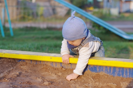 baby plays with sand on playground photo