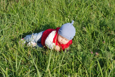 baby age of 11 months in red waistcoat on grass outdoors photo