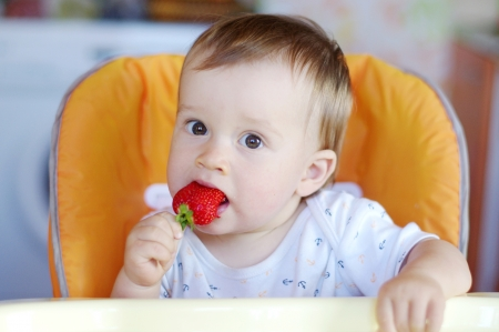 nice baby age of 1 year eats strawberry