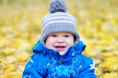 portrait of smiling baby boy age of 1 year outdoors in autumn