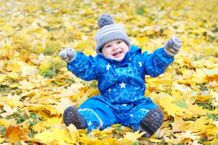 happy baby age of 1 year outdoors in autumn against yellow leaves photo