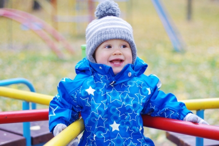 turnabout: happy smiling baby age of 1 year outdoors in autumn on playground Stock Photo