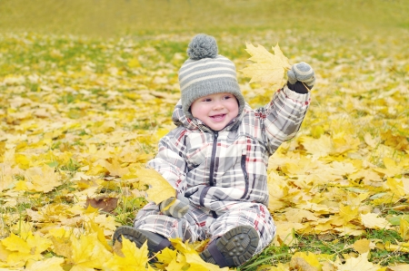 lovely baby age of 1 year outdoors in autumn against yellow leaves photo