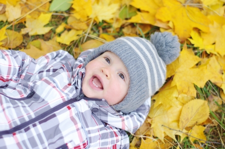 lovely baby age of 1 year outdoors in autumn against leaves photo