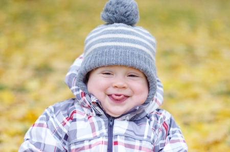 portrait of baby age of 1 year putting out tongue outdoors in autumn photo