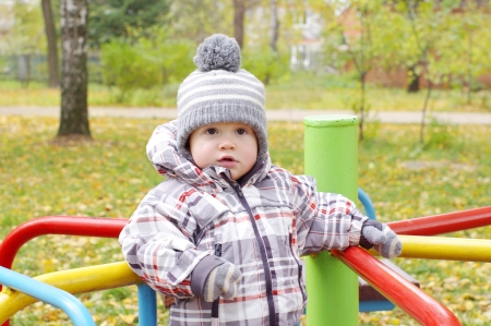 turnabout: baby age of 1 year plays outdoors in autumn on playground standing on carousel