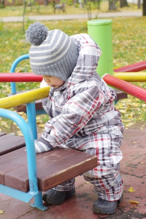 baby age of 1 year plays outdoors in autumn on playground photo