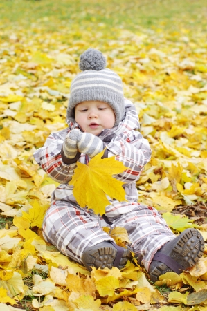 lovely baby age of 1 year outdoors in autumn with yellow leaf photo