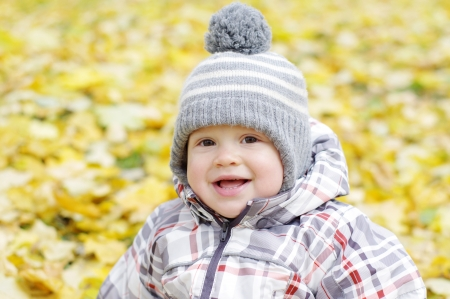 portrait of lovely smiling baby age of 1 year outdoors in autumn photo