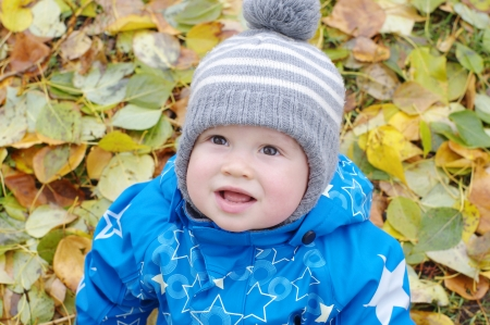 portrait of smiling baby boy age of 1 year outdoors in autumn photo