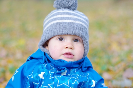 portrait of lovely baby boy age of 1 year in autumn outdoors photo