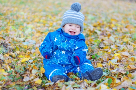 smiling funny baby boy age of 1 year sitting on yellow leaves in autumn photo