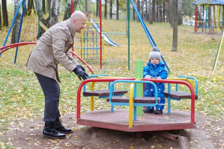 turnabout: father plays with baby son of 1 year outdoors in autumn on playground