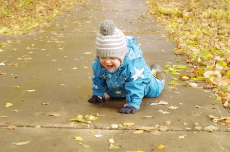 happy lovely baby age of 1 year creeps on a path in park outdoors  photo