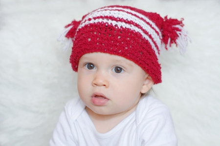 portrait of lovely baby age of 1 year in red knitted hat