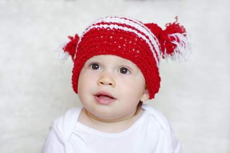 portrait of funny baby age of 1 year in red knitted hat photo