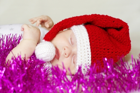 sleeping baby in New Years hat and Christmas-tree decoration photo