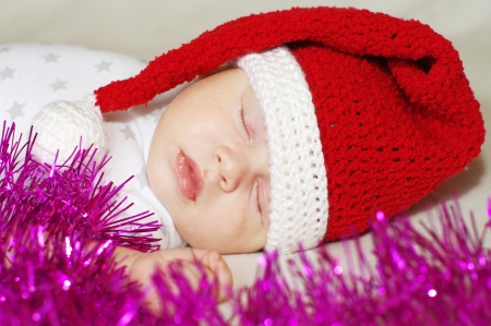 spangle: lovely sleeping baby in New Years hat among spangle Stock Photo