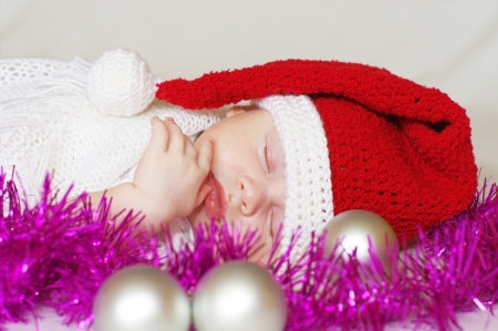 lovely sleeping baby in New Years hat waits gifts photo