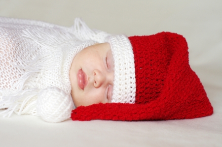 lovely baby age of 2 months sleeping in santa hat photo