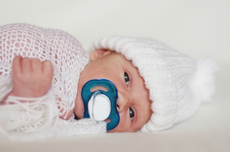 portrait of lovely newborn age of 2 weeks with dummy in white knitted hat