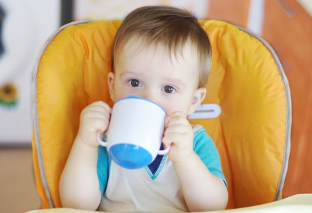 lovely baby boy age of 1 year drink from baby cup Stock Photo