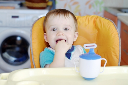 baby on chair: happy baby boy age of 1 year sitting on baby chair on kitchen Stock Photo