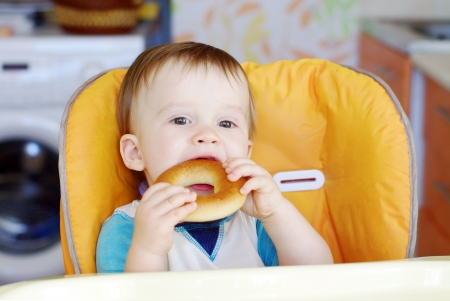 bublik: happy baby boy age of 1 year eating round cracknel on kitchen