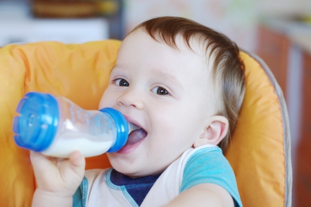 smiling baby boy age of 1 year drinking milk from a small bottle