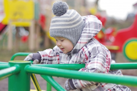 turnabout: baby age of 1 year standing on carousel outdoors in autumn Stock Photo