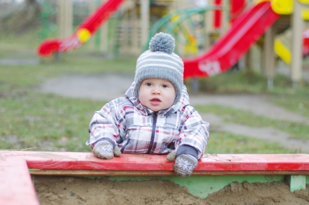 baby age of 1 year standing by sandpit on playground  Stock Photo