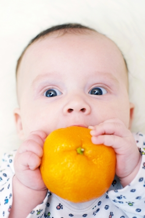 lovely baby age of 3 months with tangerine photo