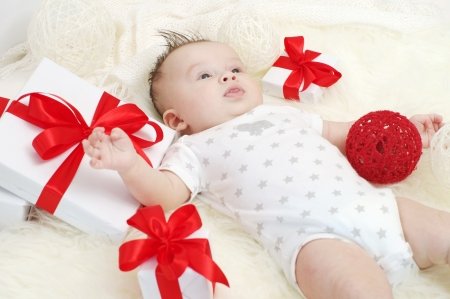 nice baby boy age of 3 months lying among gifts