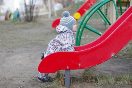 baby age of 1 year standing by slide on playground photo