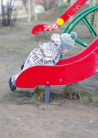 baby age of 1 year climbing on slide on playground photo