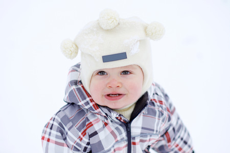portrait of lovely warm dressed baby age of 1 year in winter outdoors Stock Photo
