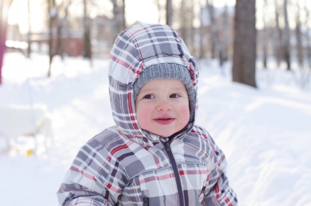 happy 1 year baby with rosy cheeks in winter outdoors