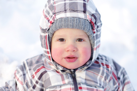 1 year baby with rosy cheeks in winter outdoors