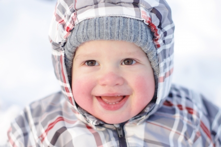 happy 1 year baby with rosy cheeks in winter outdoors photo