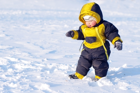 lovely 1 year baby walking in winter outdoors Stock Photo