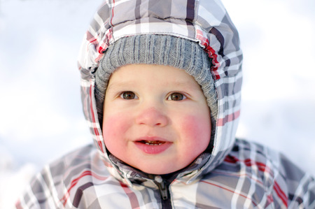 smiling 1 year baby with rosy cheeks in winter outdoors