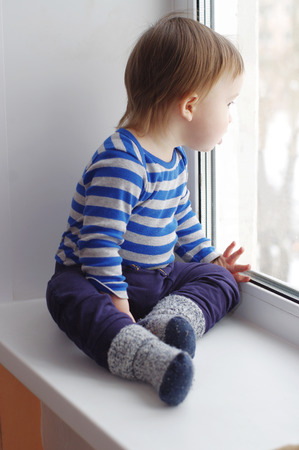 lovely baby looks out of window