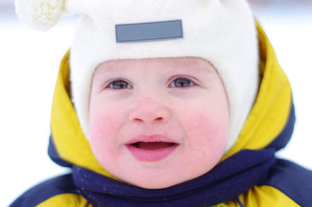 portrait of baby with rosy cheeks in winter outdoors  photo