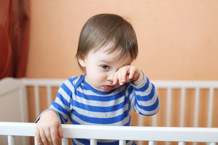 sad 1 year baby in white bed Stock Photo